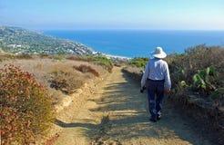 Senior man hiking hills above Laguna Beach, CA. Image shows man (senior citizen) hiking a trail through a Chaparral biome overlooking the Pacific Ocean and stock photos