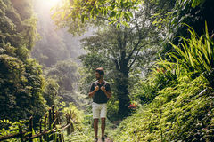 Man hiking in lush rainforest Stock Photos