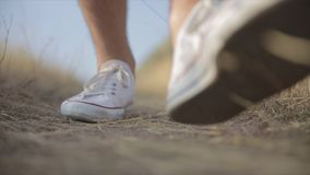 Man hiking on mountain. Young man walking into camera with his feet while he is hiking on mountain trail stock footage