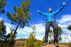 Man hiking reaching summit top cheering in forest. Man hiking reaching summit top cheering celebrating on mountain top with arms up outstretched towards the sky Stock Image