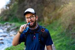 Man hiking and hydrating with water pipe stock photo
