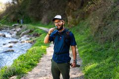 Man hiking and hydrating with water pipe royalty free stock image