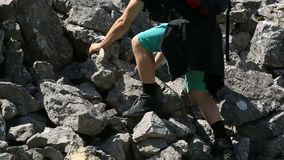 Man hiking on a rocky slope. Young man hiking on a rocky slope stock footage