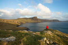 Man hiking through Scottish Highlands along rugged coastline. Man wearing red coat hiking through the rugged coastline and cliffs of the Scottish Highlands in royalty free stock photography