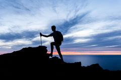 Man hiking silhouette in mountains, ocean and sunset inspiration Royalty Free Stock Images
