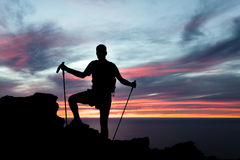 Man hiking silhouette in mountains, ocean and suns Stock Image
