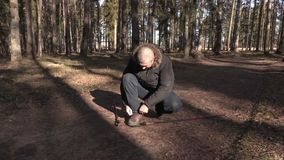 Man with hiking sticks on path tied athletic shoes stock footage