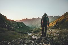 Man hiking at sunset mountains with heavy backpack