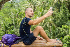 Man hiking taking selfie with smart phone. Happy young man takin Stock Photography