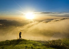 Man on a hill at sunset with camera making photo Royalty Free Stock Image