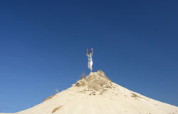Man on Hilltop. Man leaping into air, at top of white sandy hill, blue sky Royalty Free Stock Image