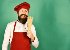 Man or hipster with beard holds macaroni on green background stock image