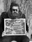 Man, hipster, with beard and moustache in black sunglasses covered with white frost gives double ok gesture with black. Board on winter day on natural royalty free stock images