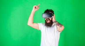 Man with hipster beard and tattoo singing along to favorite song. Brutal man with bushy beard watching rock concert in. VR headset, music concept. Bearded man stock images
