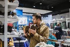 Man hipster in beige jacket choosing yellow winter boots in store - shopping, fashion, sale, ,style and people concept Royalty Free Stock Images