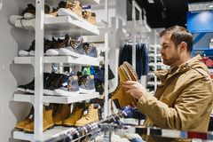 Man hipster in beige jacket choosing yellow winter boots in store - shopping, fashion, sale, ,style and people concept. Bearded man hipster in beige jacket Royalty Free Stock Photos