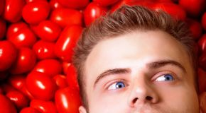 Man hipster with blue eye, farmer lies on tomatoes and dreams, looks aside royalty free stock photo