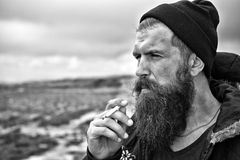 Man hipster or guy with beard and moustache smoking cigarette Royalty Free Stock Photography