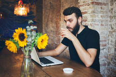Man with hipster hair style and beard is drinking coffee at loft cafe and is working with laptop royalty free stock photos