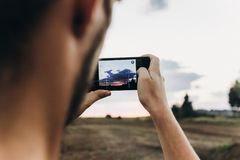 man hipster traveler taking photo holding smart phone, of beautiful sunset scenery in summer field. instagram photography. stock images
