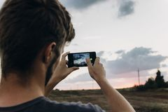 man hipster traveler taking photo holding smart phone, of beautiful sunset scenery in summer field. instagram photography. royalty free stock images