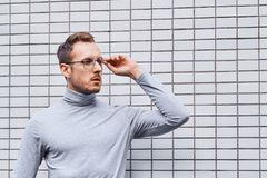 Hipster wearing glasses, standing near the wall made of small tiles. Man, hipster, wearing glasses, wearing grey turtleneck standing near the wall made of small stock photos