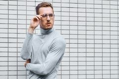 Hipster wearing glasses, standing near the wall made of small tiles. Man, hipster, wearing glasses, wearing grey turtleneck standing near the wall made of small stock photo