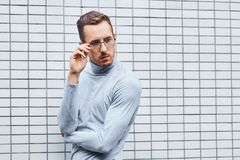 Hipster wearing glasses, standing near the wall made of small tiles. Man, hipster, wearing glasses, wearing grey turtleneck standing near the wall made of small stock photography