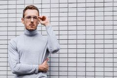 Hipster wearing glasses, standing near the wall made of small tiles. Man, hipster, wearing glasses, wearing grey turtleneck standing near the wall made of small stock images