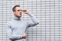 Hipster wearing glasses, standing near the wall made of small tiles. Man, hipster, wearing glasses, wearing grey turtleneck standing near the wall made of small royalty free stock photography