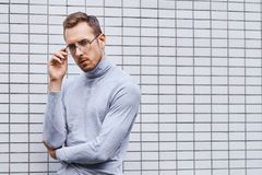 Hipster wearing glasses, standing near the wall made of small tiles. Man, hipster, wearing glasses, wearing grey turtleneck standing near the wall made of small royalty free stock photo