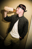 Man and His Alcohol. A man drinking alcohol from a bottle in a paper bag Stock Photo