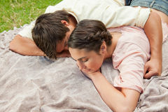 Man with his arm around his friend while lying on a blanket Royalty Free Stock Image
