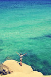 Man with his arms in the air in front of the ocean, filtered Stock Photos