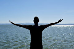 Man with his arms in the air in front of the sea. The silhouette of a young caucasian man seen from behind with his arms in the air in front of the ocean Stock Image