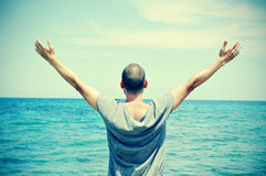 Man with his arms in the air, with a slight vignette added. Closeup of a young caucasian man seen from behind with his arms in the air in front of the ocean Stock Photo