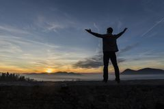 Man with his arms spread widely standing outdoors silhouetted ag Stock Photos