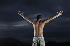 Man with his arms wide open. Young Man with his arms wide open and cloudy night scape in background Royalty Free Stock Photography