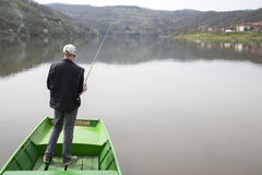 Man With His Back Towards Camera Fishing From The Boat Reeling String And Waiting Fish To Take A Bait Water Reflection Royalty Free Stock Photo