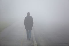 Man with his back walking through the fog street Royalty Free Stock Images
