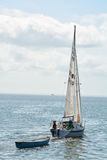 A Sail boat towing a dingy with a man and his labrador on the boat in calm waters. On Tampa bay Florida. No Model/Property Release. A man and his chocolate stock photos
