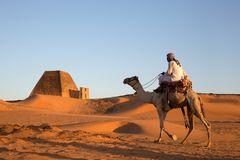 Man with his camel in a desert in Sudan Stock Images