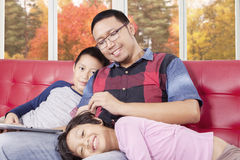 Man and his children with tablet on sofa Stock Photography