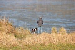 Man and His Cocker Spaniel. A man and his Cocker Spaniel enjoy a bright autumn day along the river shoreline stock images