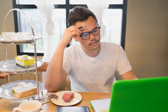 A man and his computer with thinking face at tea time Stock Image