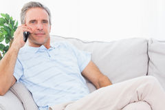 Man on his couch making phone call and smiling at camera Royalty Free Stock Images