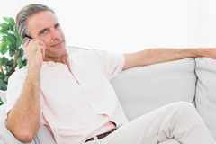 Man on his couch on the phone smiling at camera Stock Image