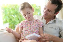 Man with his daughter playing games on a tablet Stock Photography