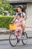 Man with his daughter on a rental bike. Beijing, China Royalty Free Stock Images