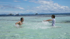 Man and his daughter splashing water in the sea. stock video footage